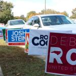row of multiple colored signs supporting local politicians in front of cars