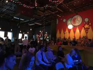 Crowd listens at open mic event in low light cafe