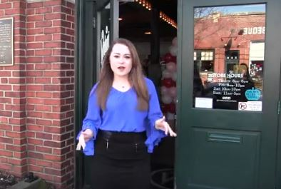 screen shot of student reporter in front of store
