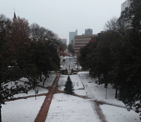 Snow covering main lawn at William Peace University and downtown in the background