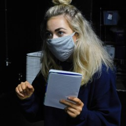 Student with mask holding notebook