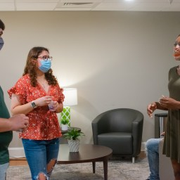 Three students with masks talk