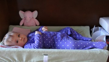 Baby on a change table wearing purple pajamas