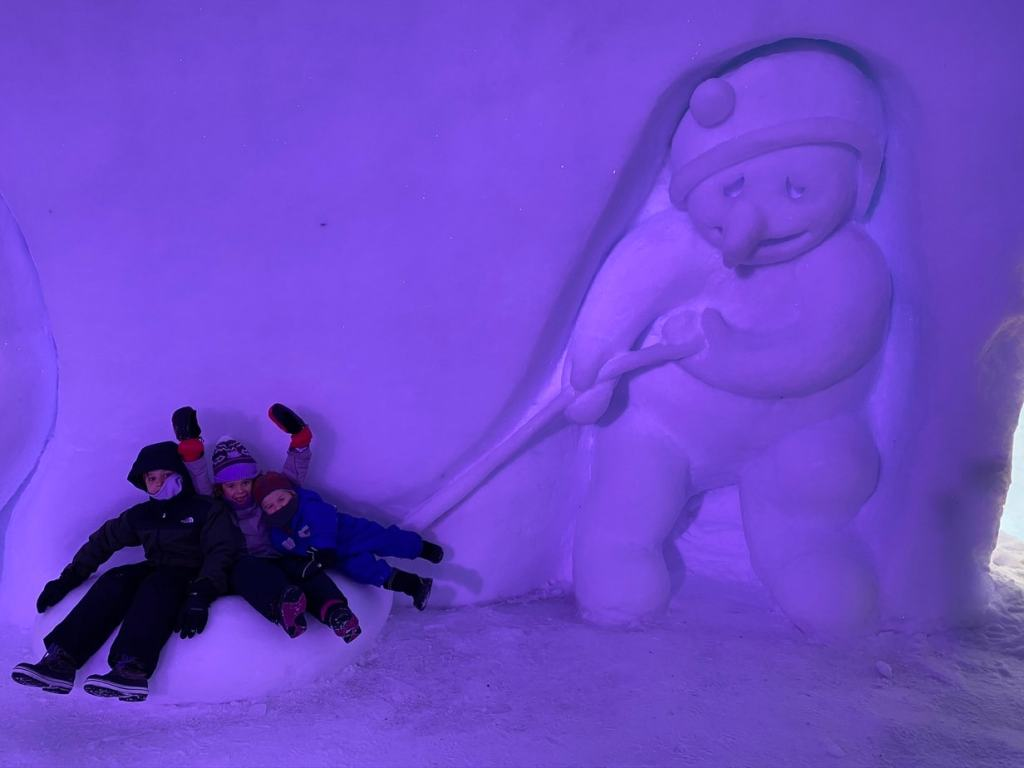 children sitting in a snow sculpture of a snowman hitting an ice puck at Snowman World
