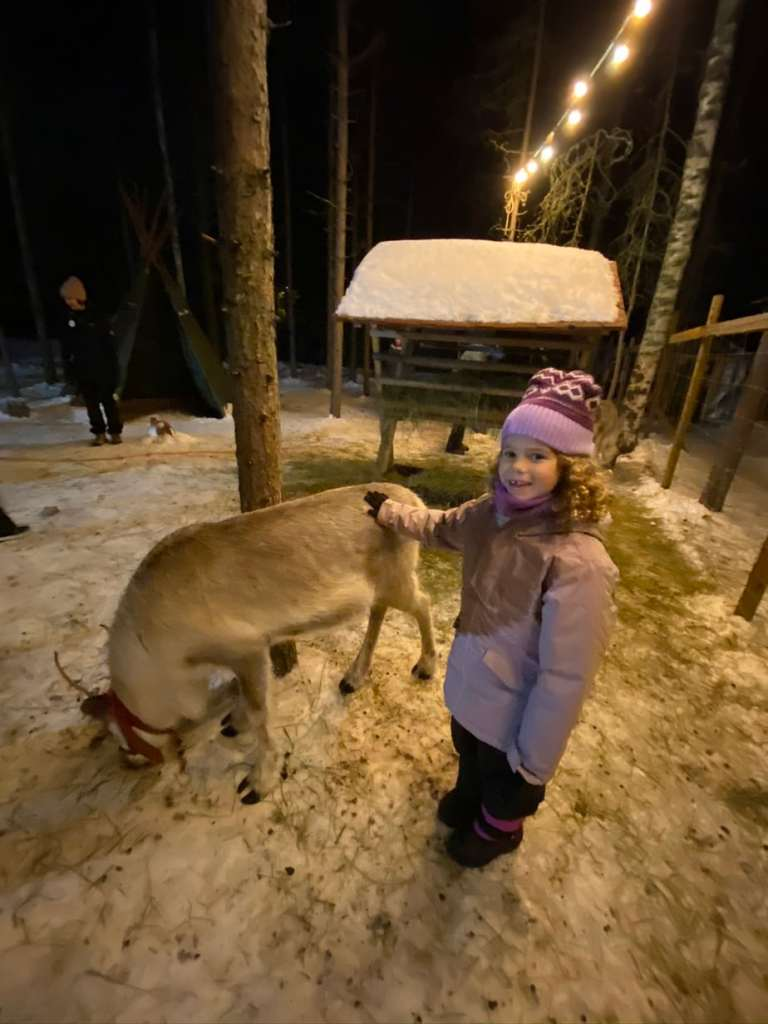 Child petting reindeer at Elf's Farm Yard in Santa Claus Village Finland