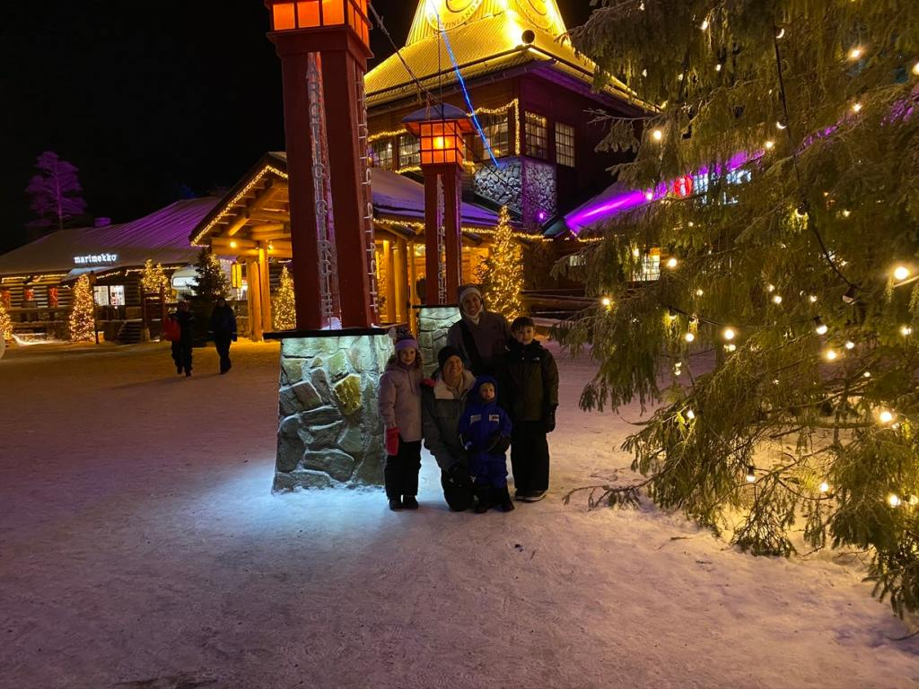 family standing in Santa Claus Village Finland under the Arctic Circle Line