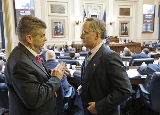 House majority leader, Del. Kirk Cox, R-Colonial heights, talks with Senate Republican floor leader, Sen. Thomas Norment, R-James City County, right during the House session at the Capitol  Thursday, Feb. 21, 2013 in Richmond, Va. The General assembly is in it's last few days for the 2013 session.   (AP Photo/Steve Helber)
