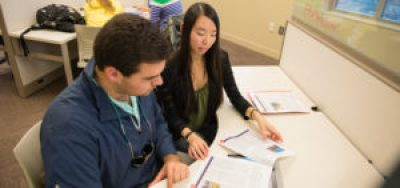 "Writing Fellows tutoring students in the Writing Center at the Academic Success Center. Also, Writing Center Director Meredith McCarroll working with a student in her office, students studying in a common area of the Academic Success Center, and a dry erase board with the ""History of Composition"" located in Daniel Hall."