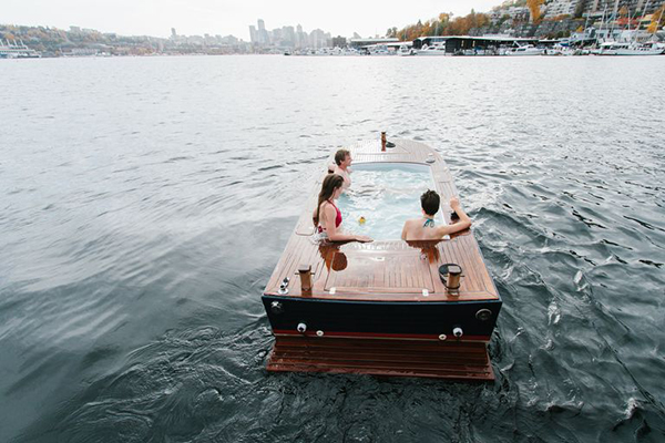Stay warm while adventuring into fall: A wooden hot tub boat floats on a lake.