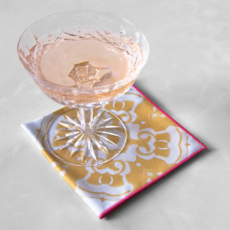 Alexandria Cloth Cocktail Napkin in daisy yellow with a crystal champagne glass