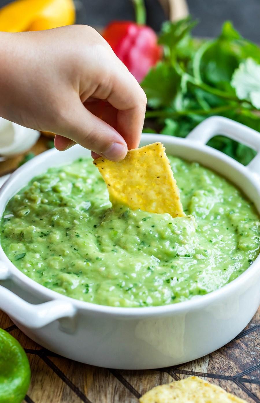 avocado salsa verde with tortilla chips action shot