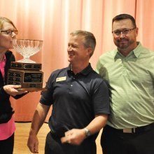 Jane Wiederhold is presented with the Developer's Cup trophy by Golf Pros Dave Vader and Ronnie Decker.