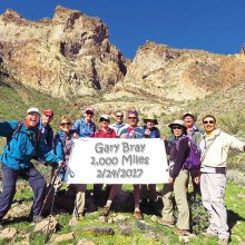Left to right: Jeff Gillen, Lynn Warren (photographer), Donna Gillen, Julie Walmsley, Susan Bernt, Les Reister, Gary Bray, Len Jeffery, Beverly Kim, Steve Duncanson and Ed Kim pausing on an unusually green slope laced with poppies on the south side of Saddle Mountain.