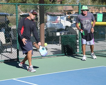 Steve Cain and Bob Chester demonstrate a serving technique called stacking, common with left-handed players; Photo by Dannie Cortez.
