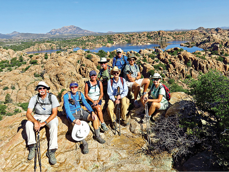 "Left to right: Wayne McKinney, Lynn Warren (photographer), Marilyn Reynolds, Dave Ausman (""Ausy""), Pete Williams (hike leader), Ed Bobigian, Diana Bedwell and Mary Hill relaxing in the Granite Dells high above Watson Lake with Granite Mountain in the background."