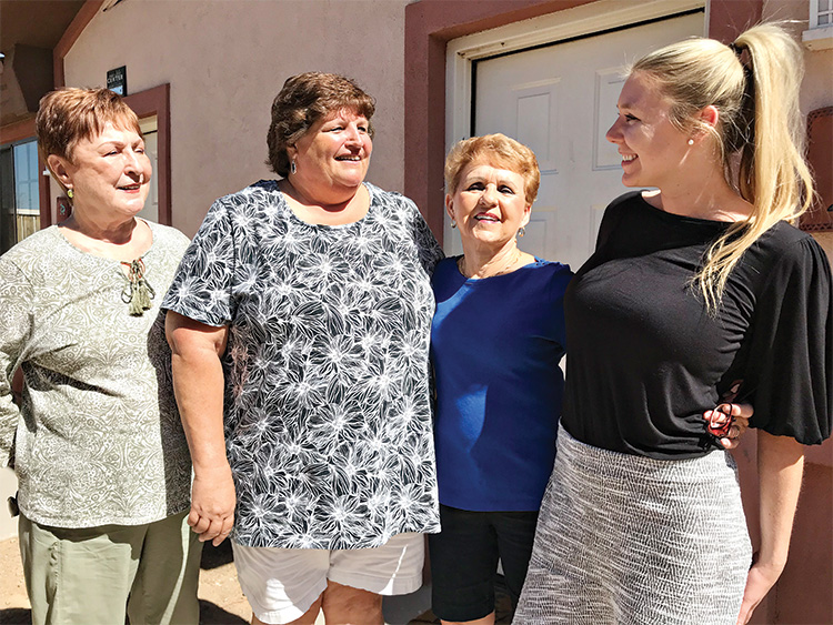A job well done. PC Singles Club volunteers (left to right) Rita Erne, Kathy Weldon and Jane Bacon accept warm thanks from Community Development Director Devin DeFendis after completing the renovation of a casita at the New Life Center.