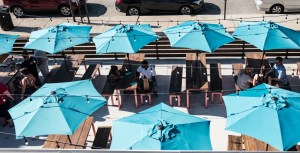 A bird's eye view of Pecan Penny's patio shows 7 teal tents on picnic tables, filled with patrons enjoying the great barbecue