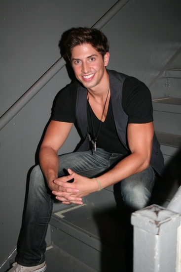 Nick Adams in a black V-neck sitting on stairs.