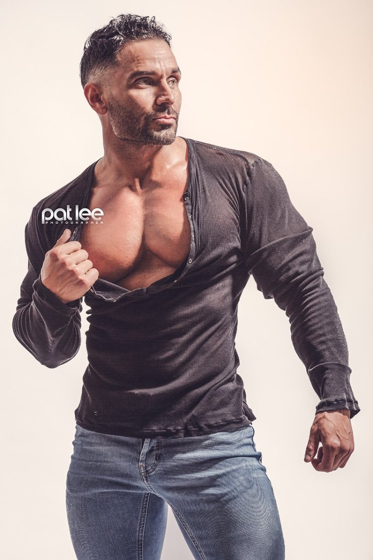Bodybuilder Ryan Stanton posing in a Henley, pulling the collar slightly. Taken by Pat Lee.