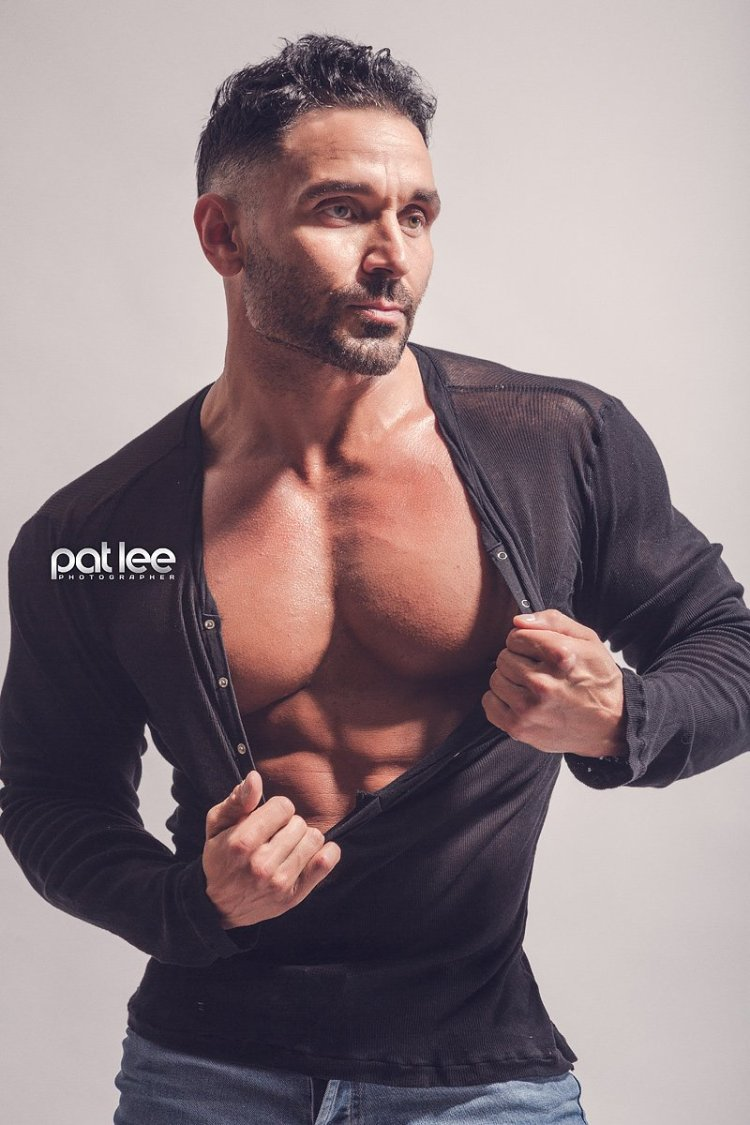 Bodybuilder Ryan Stanton posing in a Henley, stretching it down to his abs Taken by Pat Lee.