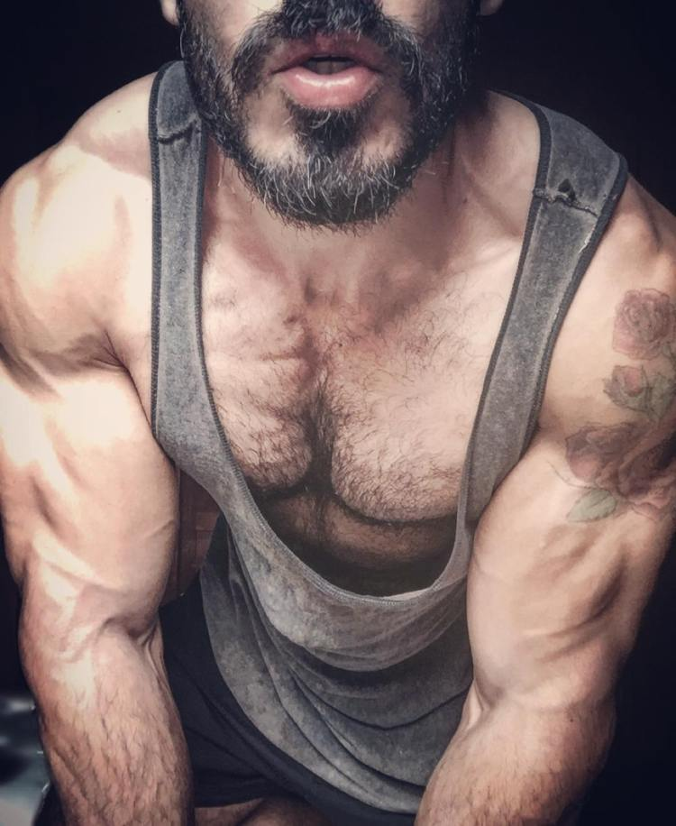 Pedro Augusto showing hairy pecs from seductive viewpoint in grey tank top.