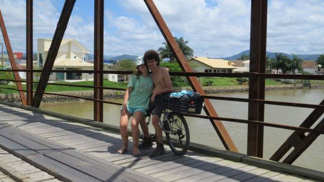 A Larissa e o Fê na ponte do Rio Tijucas viajando em direção a Morretes