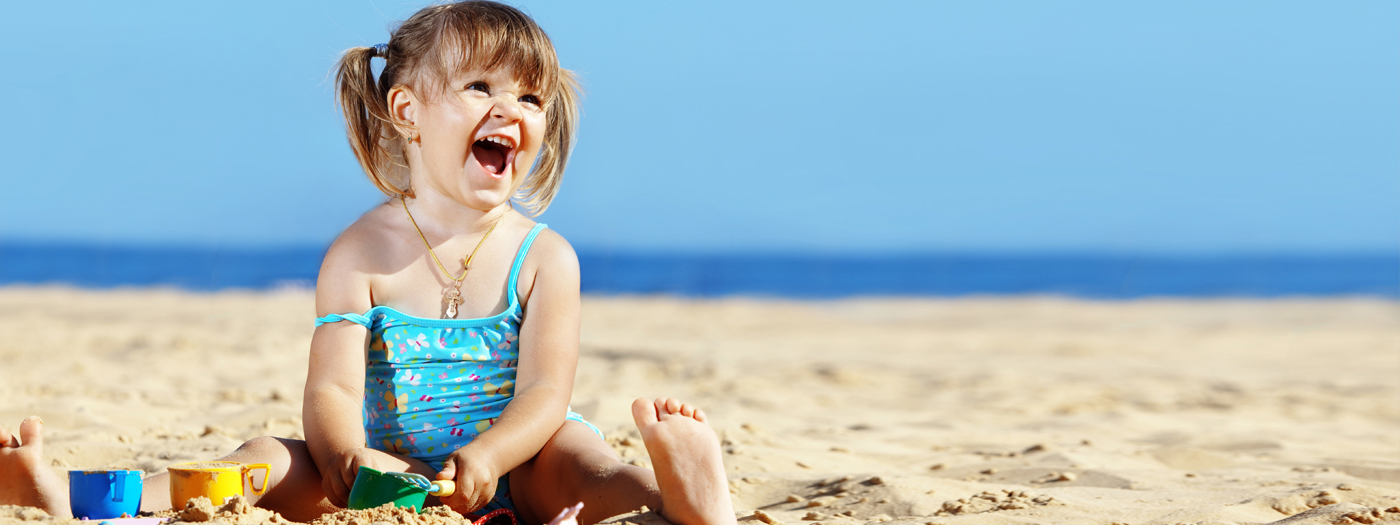Young girl having fun playing in the sand at the beach