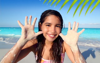 Pre-teen girl with sandy hands holding them up and smiling