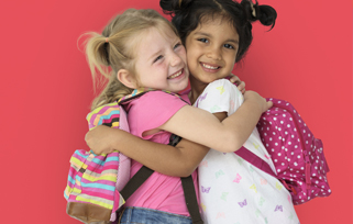 Two young girls wearing backpacks, hugging & smiling