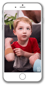 Kid shows off bandage during a virtual appointment with a pediatrician