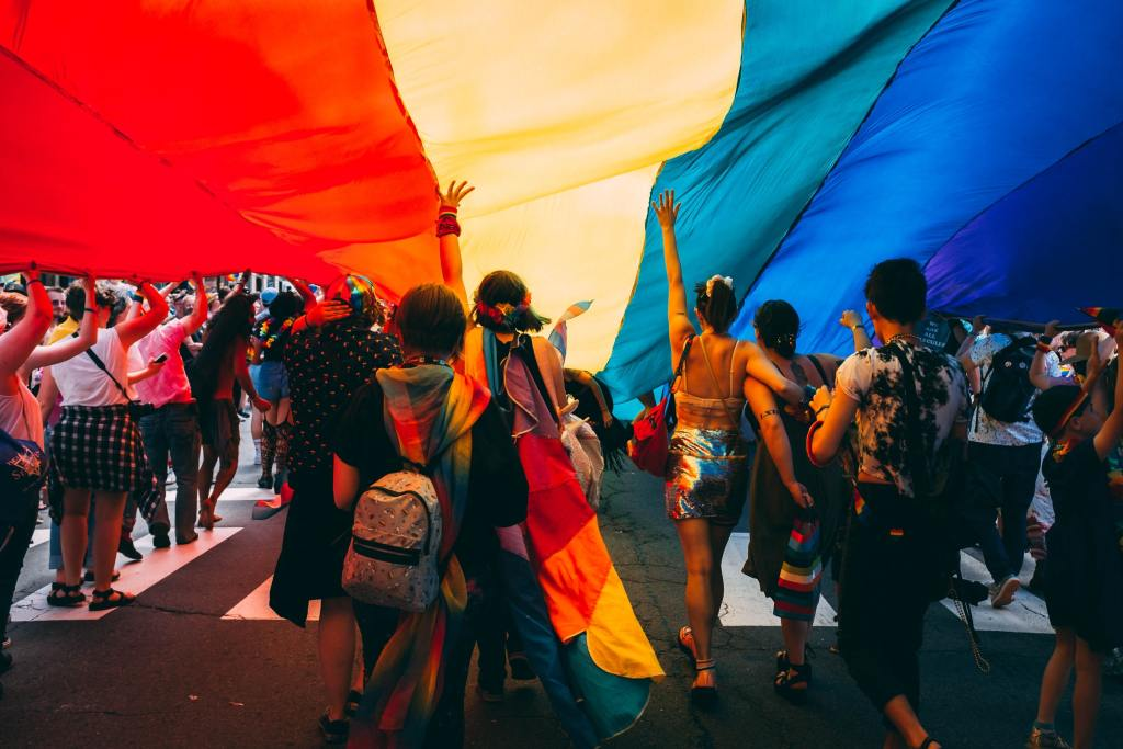 People under a very large rainbow-colored piece of cloth
