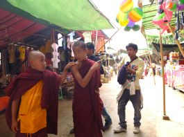 Monks checking out DVDs and T-Shirts in Inlay Lake market. Should they go for Expandables 2?