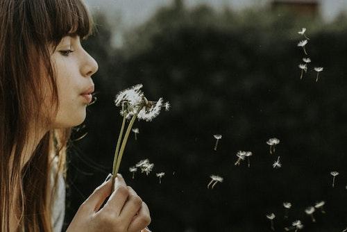 Mujer soplando flor