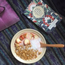 Toppings are slices peach, granola and desiccated coconut.