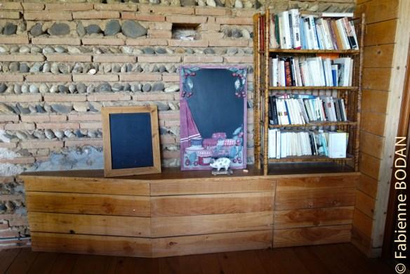 En haut de l'escalier en bois, une terrasse avec bibliothèque. © Fabienne Bodan