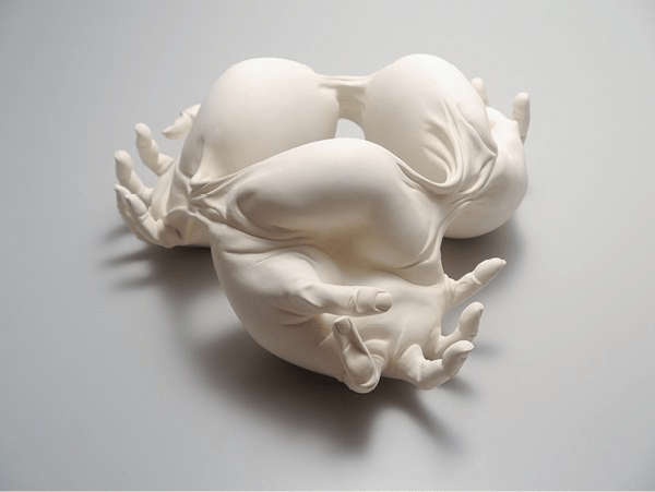 white sculpture of contorted hands