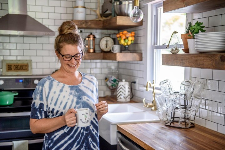woman in a blue tie-dyed shirt standing in her kitchen holding a mug