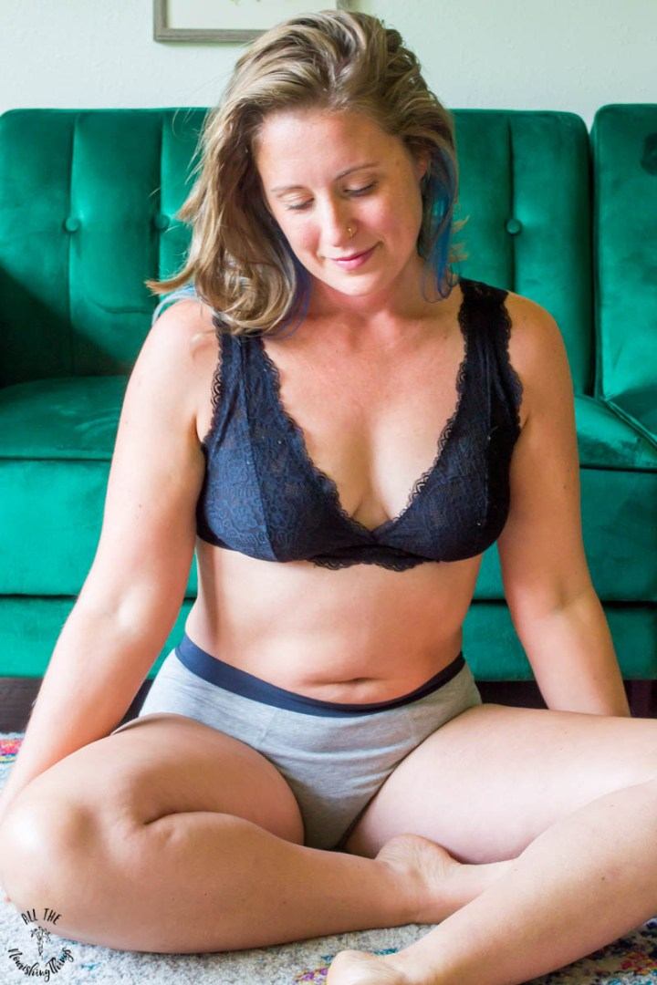lindsey lockett thoughtfully looking at the floor while sitting and wearing a black bra and grey period panties