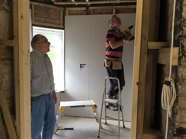 Mike putting up the plasterboard with Tim