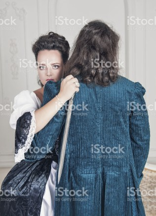 Beautiful young woman in medieval dress with dagger hugging man