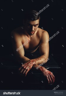 stock-photo-beautiful-pumped-man-with-a-naked-torso-and-a-tattoo-hands-in-the-blood-halloween-posing-on-a-393879406