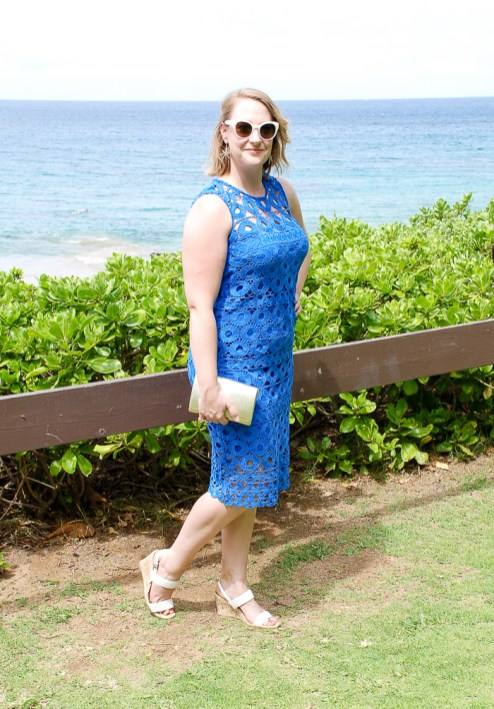 Wedding guest attire: blonde woman stands before ocean in blue crochet dress perfect for beach wedding.
