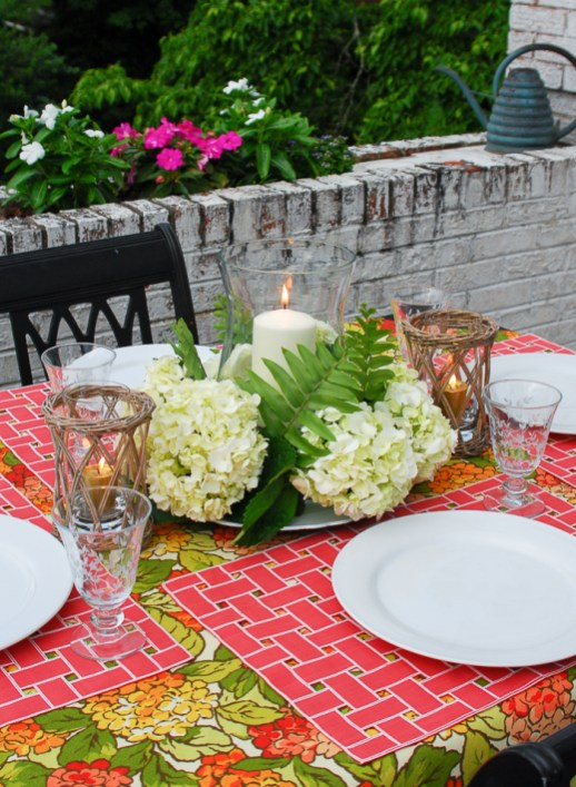 Hydrangea tablescape with coral placemats, hydrangea centerpiece with hurricane lantern, and colorful hydrangea tablecloth