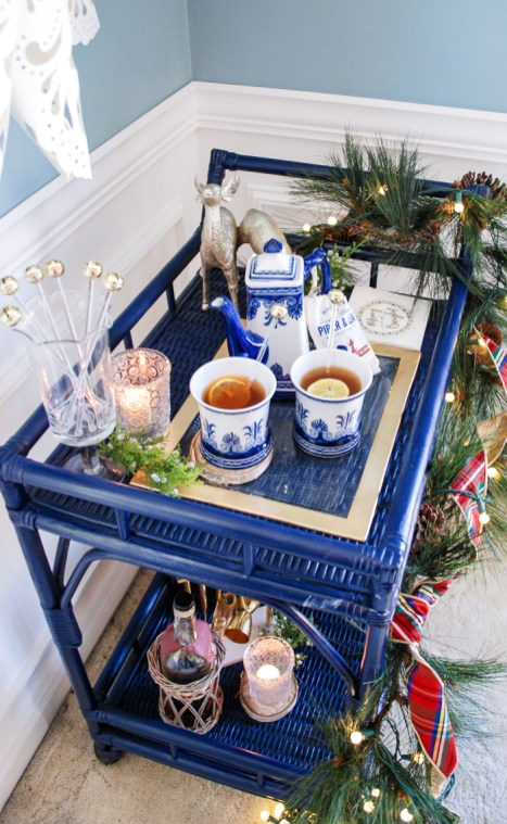 Lemon berry hot toddy on blue rattan bar cart decorated for the holidays with pine and plaid.