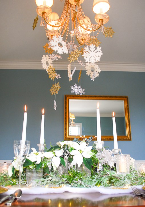 Winter tablescape tutorial for frosted forest table with snowflakes hung from chandelier
