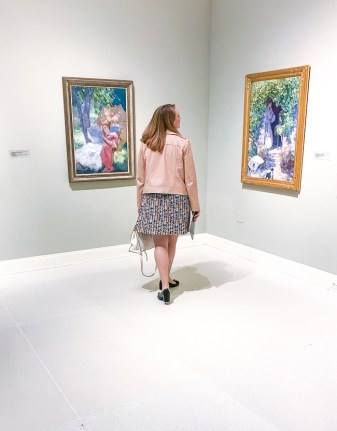 Blond woman standing in art museum in front of colorful paintings by Catherine Wiley