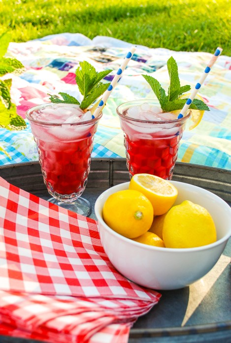Blueberry lemon mint fizz drinks on a tray with lemons.