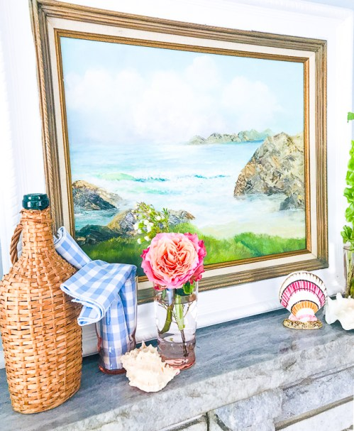 A nautical summer mantel with vintage coastal painting, wicker cask bottle, and seashells.