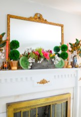traditional fall mantel with fall dish garden, boxwood topiaries, majolica spaniels, magnolia, and gilt mirror.
