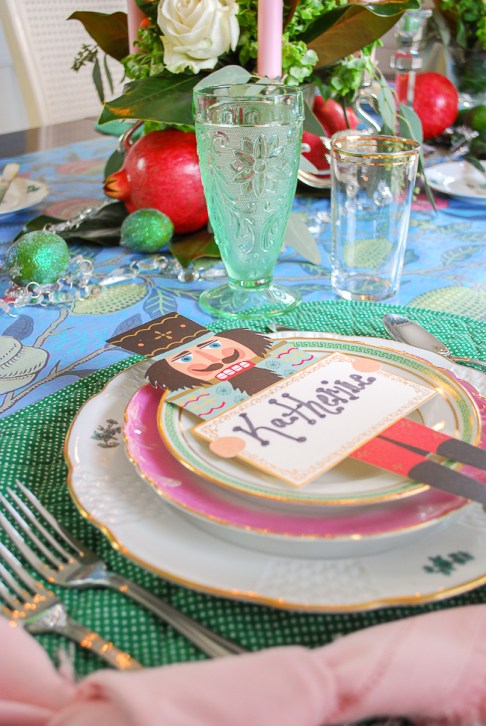 Whimsical place setting with pink and green china and paper nutcracker place cards